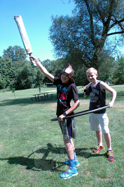 "Jason Pansa, left, and Matthew Jaeger held a hula hoop around them as a ""ship"" to navigate around the ""sky,"" which was represented by all the grass at Dickinson Memorial Park. (Hallabeck photo)"