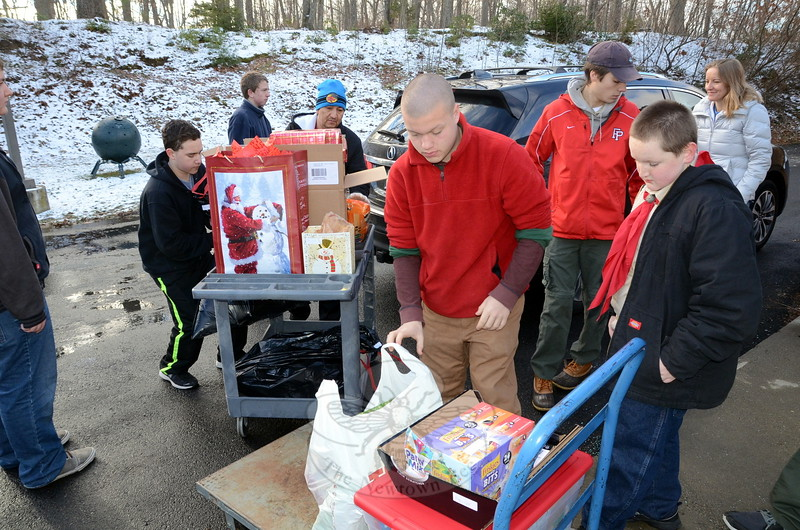 """The Frasier Woods School was buzzing with activity December 13 as Boy Scouts and leaders from Troop 370 at Newtown UMC joined residents and volunteers from The Newtown Fund either dropping off or delivering toys, gifts, and food to residents in need during the annual Depot Day event. Dozens of referrals through the town's Social Service Department or local clergy were gladly accepted by residents like Stacy White, pictured with volunteers loading a delivery for a mom and two teens her family """"adopted"""" for the holidays. Scouts Matt Tassiello and Jacob Markowsky also assisted All-Star bus company staffer Joe Colangelo who was dropping off donations for two local families receiving holiday gifts and food collected by local bus drivers. (Voket photo)"""
