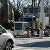 A compact passenger vehicle, left foreground, is dwarfed by a fuel tanker truck, right, and a flatbed tractor-trailer truck, center, at the Main Street flagpole intersection this week. Trinity Episcopal Church, left background, stands at one of the corners of the five-way intersection. A state Department of Transportation official is offering some ideas on how traffic flow can be improved at the intersection.(Gorosko photo)
