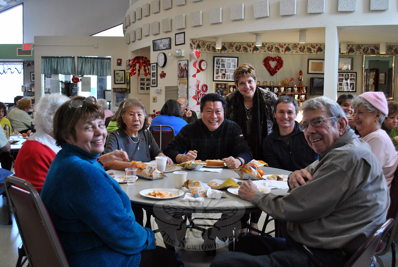 From left, Diane Baker, Heidi Roesch, Chico Bierlot, State Senator Tony Hwang, Senior Center Director Marilyn Place, architect Tom Arcari, Rose Cippola, and Ray Baker enjoy Hot Dog Day at the Newtown Senior Center. Sen Hwang was on hand to dish and dine. (Crevier photo)