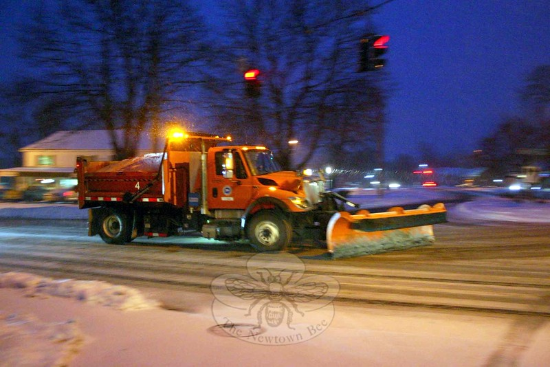 """A Connecticut DOT truck heads west on Church Hill Road Monday night, passing through the Queen Street intersection. """"Rush hour"""" was anything but rushing, with many people taking the advice of town and state officials to get off the roads as early as possible once Winter Storm Juno arrived. (Hicks photo)"""