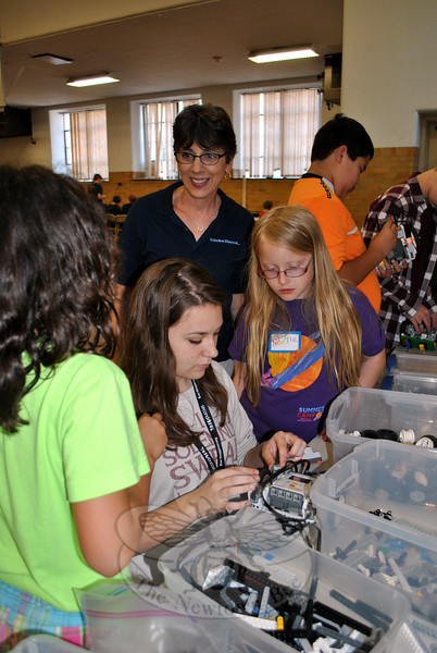 Mentor Charlee Stewart, center, helps Noelle Fogal, right, and Madison Singlak select pieces to upgrade their robots, Thursday morning, June 25, while Robotics And Beyond instructor Donna Didsbury looks on. (Crevier photo)