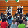 """Sandy Hook Elementary School retirees, art teacher Leslie Gunn and secretary Joanne Didonato, left and right respectively, sat in their wooden rocking chairs during the school's awards ceremony on June 15. The rocking chairs were just one of the gifts given to the women during the event. """"This is just something I didn't expect,"""" said Ms Didonato. (Hallabeck photo)"""