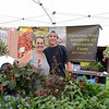 Sara Blersch and Nick Harper sold hanging flower baskets and vegetables at the 2015 Farmers Market on the Fairfield Hills opening day Tuesday, but were promptly cut short by a downpour. They quickly packed away their goods from Daffodil Hill growers, Woodside Farm, in Southbury. (Bobowick photo)