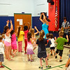 """While the threat of an early summer storm moved the Summer Jam Concert Series opener to an indoor venue this week, the enthusiasm of children and adults like filled the gym at Hawley School with enough happy energy that the last-minute change of plans was quickly overcome. Vanessa Trien and The Jumping Monkeys opened this year's season of free concerts on June 23, and a few hundred people crowded into the Church Hill Road location to enjoy the show. Here, Ms Trien was introducing children to """"Bubble Ride,"""" one of the songs she and her band performed Tuesday afternoon. Children spun, twirled, giggled, laughed and danced their way through this song and every other one that made up the approximately 75-minute show. Ms Trien, standing near the center, was joined by her band. Seen at right, along the stage, are Paul Kochanski, Dave Jamrog and (partially hidden) Adam Rothberg. (Hicks photo)"""
