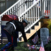 Marine Sergeant Dustin Gill lays a white carnation at the headstone memorializing fallen soldiers at VFW Post 308. A wreath and three carnations — red, white, and blue — are placed there each Memorial Day. (Crevier photo)