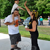 "Kat Holick, Newtown's dancing traffic agent, high-fives 3-year-old Ryan Costa, seated on father Gary Costa's shoulders. Ryan's mother, Julie Barbeau, challenged Ms Holick to take on TV talk show host Ellen Degeneres's ""Just Keep Dancing"" challenge, to raise awareness of pediatric cancer. Ryan is currently undergoing treatment for leukemia, ""and doing really well,"" according to Ms Barbeau. Approximately two dozen people popped up on the Dickinson Park field Monday morning, May 25, to join Ms Holick and Ryan, as they danced to ""Play It Again"" by Luke Ryan, with sound provided by Linda Perrault. ""I'm honored!"" exclaimed Ms Holick. ""That little boy has the cutest smile you've ever seen."" A video of the challenge will be sent to Ellen Degeneres, said Ms Holick, who issued a continuing challenge to ""Just Keep Dancing"" to pop stars Pink and Cher, and Laurie Pineau and the Sunshine Kids. ""I just wanted [Kat] to do a video of herself. I never thought it would get this big,"" laughed Ms Barbeau. (Crevier photo)"