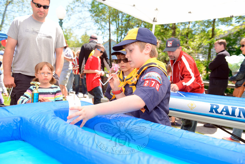 Den 5 Boy Scout Matt Majeau demonstrated how wind against the sail propels a ship. He blew through a straw at a paper sail on a toy boat, pushing it through the shallow display Saturday, May 23, during the annual Great Pootatuck Duck Race, hosted by the Lions Club. (Bobowick photo)