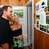 Ross and Cindy Utter step indoors at the Holcombe Hill Preserve property where they read a poster describing several of the Newtown Forest Association's preservation efforts. (Bobowick photo)