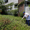 Fheila McCoy searches bushes outside a abandoned home Sunday, July 21, 2013, in East Cleveland, Ohio. Police Chief Ralph Spotts told volunteers checking vacant houses in a neighborhood where three bodies were found wrapped in plastic bags that he believes there could be one or two more victims. (AP Photo/Tony Dejak)