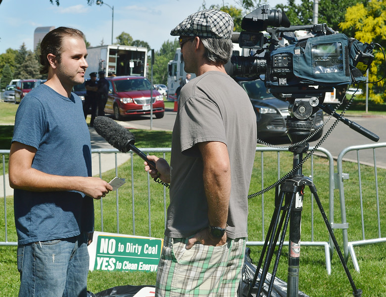 Representative of 350 Colorado being interviewed by TV news reporter.