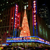 The joys of the season are celebrated city-wide in Manhattan; here is New York's Radio City Music Hall with a brilliant red Christmas tree. A marvel of Art Deco, and of the holiday.