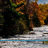 Diamonds of sunlight and crimson autumn foliage embrace sparkling Sherry Rapids along the wild Wolf River (USA WI White Lake)