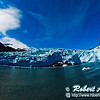 The Aialik Glacier flowing into Aialik Bay of the Pacific Ocean under blue skies within Kenai Fjords National Park on the Kenai Peninsula (USA Alaska Seward)