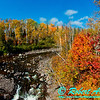 Blazing autumn foliage and bright blue skies embrace the steep shores of the Cascade River upstream of the MN Highway 61 bridge near the Lake Superior Hiking Trail within Cascade River State Park (USA MN Lutsen; RAO 2012 Nikon D800 Image 6432)