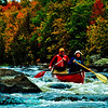 Crimson autumn foliage frames a tandem canoe in Little Slough Gundy Rapids on the wild Wolf River (USA WI White Lake)