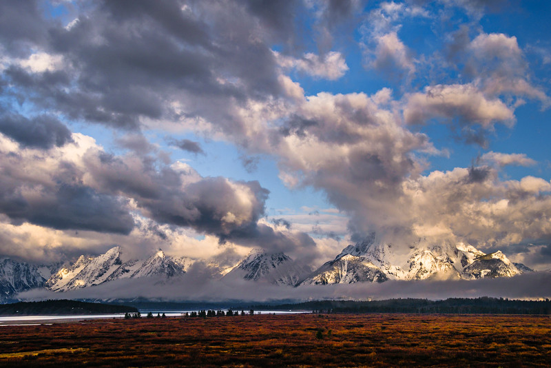 """Lightscapes in Grand Tetons National Park""  The clouds and lighting were amazing when I was here in the Grand Teton National Park.  The sun would peak through on the mountains revealing the snow covered peaks.  This was at the end of May when the park was just awakening after a long winter.  I love the way the blue skies peak around the clouds letting the light through.  We didn't see the Grand Tetons much during the 5 days I was there!  Yet another amazing National Park that we have."