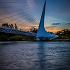 The Sundial Bridge (also known as the Sundial Bridge at Turtle Bay) is a cantilever spar cable-stayed bridge for bicycles and pedestrians that spans the Sacramento River in Redding, California, United States and forms a large sundial. It was designed by Santiago Calatrava and completed in 2004 at a cost of US$23,500,000. The bridge has become iconic for Redding.<br /> <br /> The Sundial Bridge provides pedestrian access to the north and south areas of Turtle Bay Exploration Park, a complex containing environmental, art and history museums and the McConnell Arboretum and Gardens. It also forms the gateway to the Sacramento River Trail, a 35-mile-long trail completed in 2010 that extends along both sides of the river and connects the bridge to the Shasta Dam. Drift boats of fishermen are often seen passing beneath the bridge as they fish for salmon, steelhead and rainbow trout. In the distance, Mount Shasta is barely visible. Shasta Bally is visible to the West looking upstream the Sacramento.<br /> <br /> he support tower of the bridge forms a single 217 foot (66 metre) mast that points due north at a cantilevered angle, allowing it to serve as the gnomon of a sundial; it has been billed as the world's largest sundial,although Taipei 101 and the associated sundial design of its adjoining park are much larger. The Sundial Bridge gnomon's shadow is cast upon a large dial to the north of the bridge, although the shadow cast by the tower is exactly accurate on only one day in a year – the summer solstice, June 20 or 21. The time is given as Pacific Daylight Time. The tip of the shadow moves at approximately one foot per minute so that the Earth's rotation about its axis can be seen with the naked eye.<br /> <br /> The Sundial Bridge is a cantilever spar cable-stayed bridge, similar to Calatrava's earlier design of the Puente del Alamillo in Seville, Spain (1992). This type of bridge does not balance the forces by using a symmetrical arrangement of cable forces on each side of its support tower; instead, it uses a cantilever tower, set at a 42-degree angle[9] and loaded by cable stays on only one side. This design requires that the spar resist bending and torsional forces and that its foundation resists overturning. While this leads to a less structurally efficient structure, the architectural statement is dramatic. The bridge is 700 feet (213 m) in length and crosses the river without touching the water, a design criterion that helps protect the salmon spawning grounds beneath the bridge. The cable stays are not centered on the walkway but instead divide the bridge into a major and minor path.<br /> <br /> The cable for the bridge totals 4,342 feet and was made in England. The dial of the sundial and a small plaza beneath the support tower are decorated with broken white tile from Spain. The bridge's deck is surfaced with translucent structural glass from Quebec, which is illuminated from beneath and glows aquamarine at night. The steel support structure of the bridge was made in Vancouver, Washington and transported in 40-foot sections by truck to Redding.<br /> <br /> Plans for the Sundial Bridge began in the 1990s, when the city of Redding budgeted $3 million for a pedestrian bridge across the river. However, costs escalated after Calatrava's design was chosen in 1996. The bridge was completed in 2004, three years later than originally planned, at a cost of $23.5 million, with funding from the Redding-based McConnell Foundation.The expense was justified on the basis that it would increase tourism in the Redding area, which also features Shasta Dam as another architectural marvel, and it has been successful in that goal.