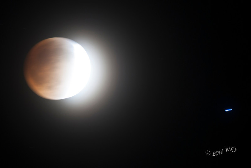 Lunar Eclipse, Long exposure (13 seconds) to show transformation to red as moon enters earth's shadow. The blue streak on the right is a star and this shows the earths rotation in the 13 second time frame