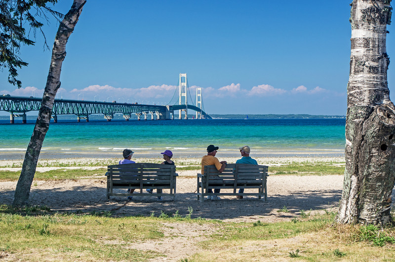 Old friends enjoy a summer's afternoon in Mackinaw City in front of The Mackinac Bridge which connects the Upper and Lower Peninsulas of Michigan.