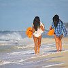 Cute girls are walking on the beach.