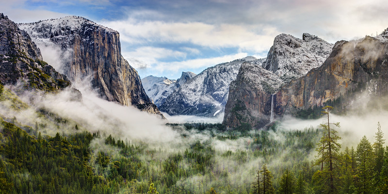 """""""Tunnel View Panorama of Yosemite National Park 2014""""  A new image of a classic Tunnel View Panorama in Winter in Yosemite National Park.  Capturing the fog and clouds swirling in the valley with Bridalveil Falls trickling and El Capitan standing proud.  Half Dome is tucked away in the back covered with snow.  The blue skies peeking through this majestic view.  The green trees with the fog standout nicely."""