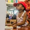 "A girl uses the self checkout machine at Lois Hole while her mother, ""Maroro Zinyemba"", watches.<br /> <br /> Taken on July 11, 2014 by James Cadden."