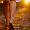 Woman_walking_into_sunset_with_bare_feet