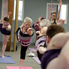 MARY SCHWALM/Staff photo Elaine Brophy holds a pose during a Bikram Yoga class in North Andover.