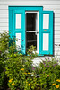 A window with decorative shutters in the house barn at the Mennonite Heritage Village in Steinbach, Manitoba, Canada.