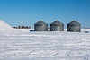 Grain bins on a snow covered field near Lowe Farm, Manitoba, Canada.