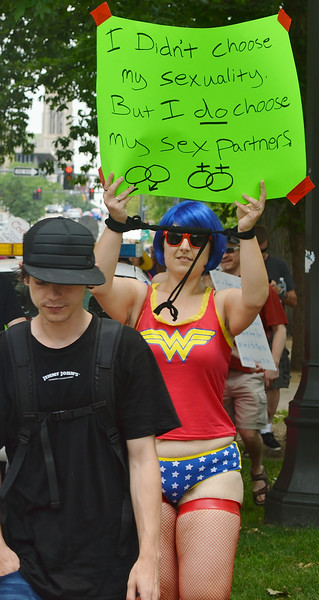 "Woman wearing blue wig and ""Wonder Woman"" costume holds up sign about sexuality, other anti-rape protesters march behind her."