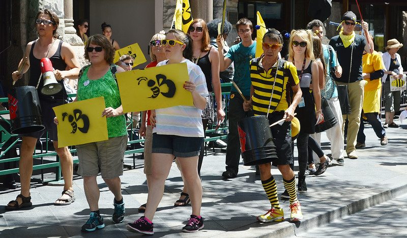 Group on marchers carrying signs with bees on them, one protesters in bee costume palying drum made from bucket.