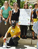 Man wearing gas mask, holding bullhorn, woman behind him holds sign about bees and pesticides.