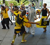 People in bee costumes pretending to die from being sprayed with pesticides by person in hazardous materials suit, face mask.
