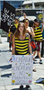 Young woman in bee costume holding sign about saving the bees, large flag behind her.