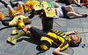 People in bee costumes pretending to die from being sprayed with pesticides.