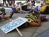 "Protester in bee costume pretending to be dead, holding video camera, ""Give Bees A Chance"" lying on their head, other in background lying down."