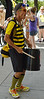 Man wearing bee costume, playing drum made from bucket.