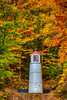 A hillside lighthouse beacon with fall foliage color in Munising, Michigan, USA.