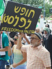 Man raises sign about Palestine above head, sign has writing on it in (Arabic??, Hebrew??), other marchers with signs in background.