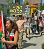 Man raises sign about Palestine above head, sign has writing on it in (Arabic??, Hebrew??), young girl carrying Palestinian flag in foreground, marchers with signs in background.