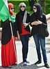Three young women wearing hijabs, standing, talking, one holds Palestinian flag on pole.