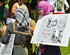 """Woman wearing hijab, holds sign with picture of Muslim girl holding sign with """"Stop Killing Us"""" on it."""