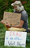 Veteran sitting, holding signs asking for help and comparing Iraq to Viet Nam.