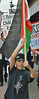 Young boy marching in protest, carrying Palestinian flag, other demonstrators with signs behind him.
