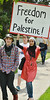 Young Muslim girl wearing headscarf, raises sign about Palestine above head, other marchers next to her.