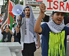 Young man wearing Kiffeya on head, carrying bullhorn, young boy carrying Palestinian flag behind him, other marcher in front of them.