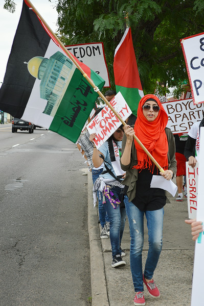 Young woman wearing red headscarf, carrying Palestinian flag with picture of mosque on it, other marchers with signs and flags behind her.