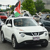 Young boy smiling, waving Palestinian flag out of top hatch of car in traffic, two young women in car with him.
